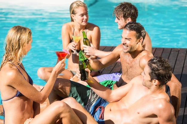 Amici felici che godono in piscina