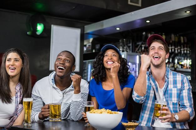 Amici felici che guardano lo sport