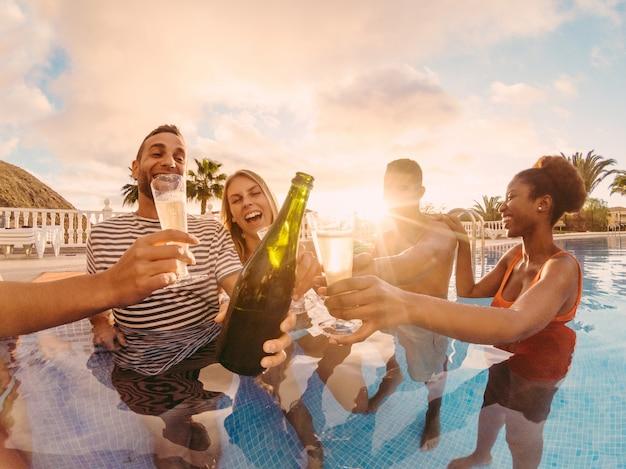 Amici felici che incoraggiano con champagne in festa in piscina al tramonto
