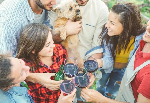 Amici felici che incoraggiano con i bicchieri di vino rosso all'aperto