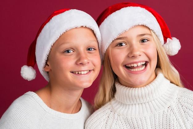 Amici felici che indossano cappelli di babbo natale