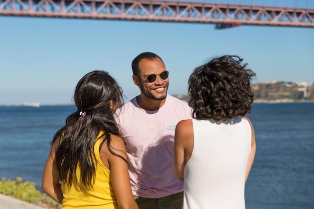Amici felici che parlano vicino al fiume