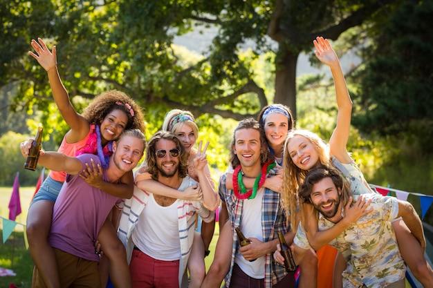 Amici felici che propongono insieme al campeggio