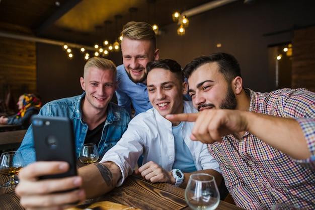 Amici felici che si siedono nel ristorante prendendo selfie