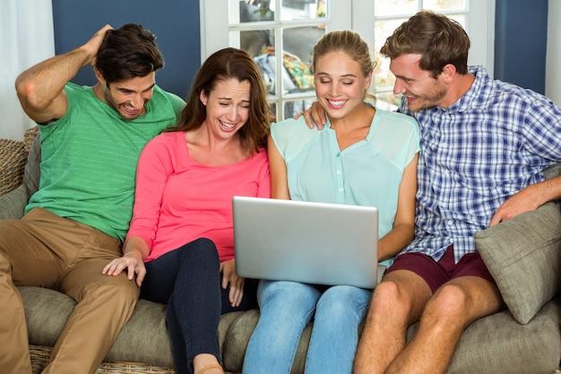 Amici felici che si siedono sul sofà e che per mezzo del computer portatile