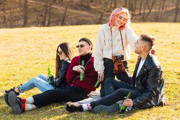 Amici felici che si siedono sull'erba e che hanno picnic con birra