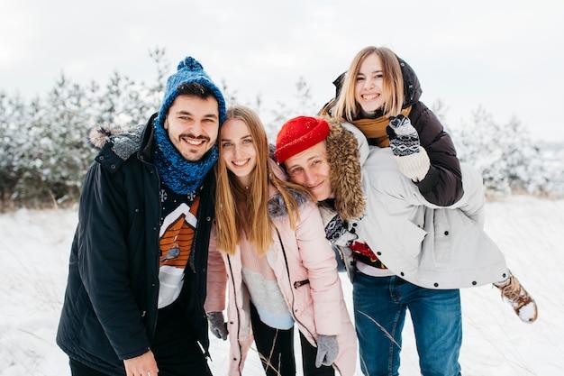 Amici felici che stanno nella foresta di inverno