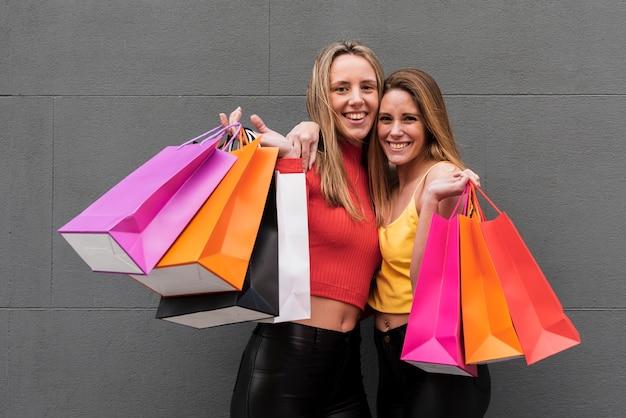 Amici felici che tengono i sacchetti della spesa