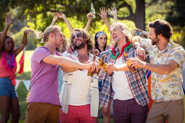 Amici felici che tostano le bottiglie di birra al campeggio