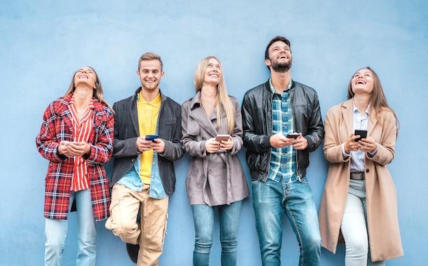 Amici felici che usano gli smartphone