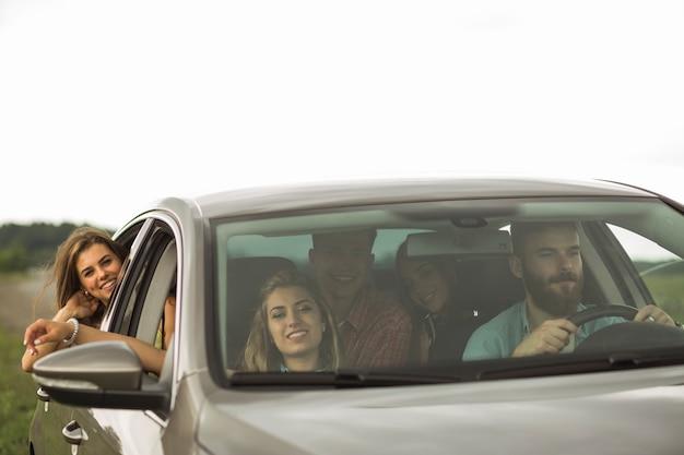 Amici felici che viaggiano in auto di lusso