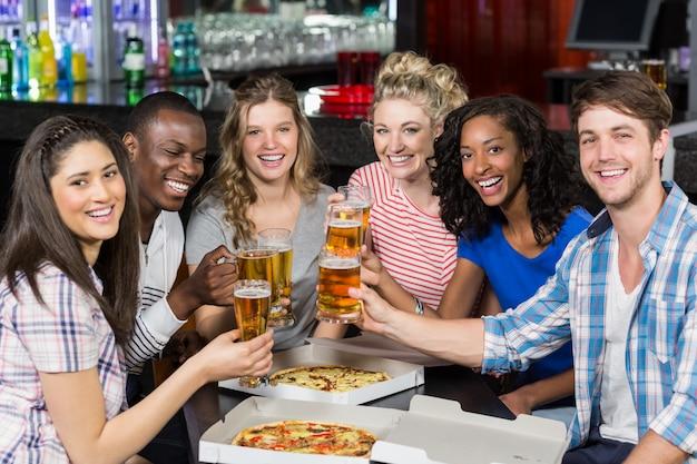 Amici felici con un drink e una pizza