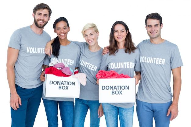 Amici felici dei volontari che tengono le scatole di donazione