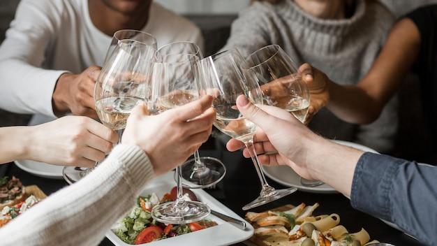 Amici felici del primo piano che tostano i bicchieri di vino