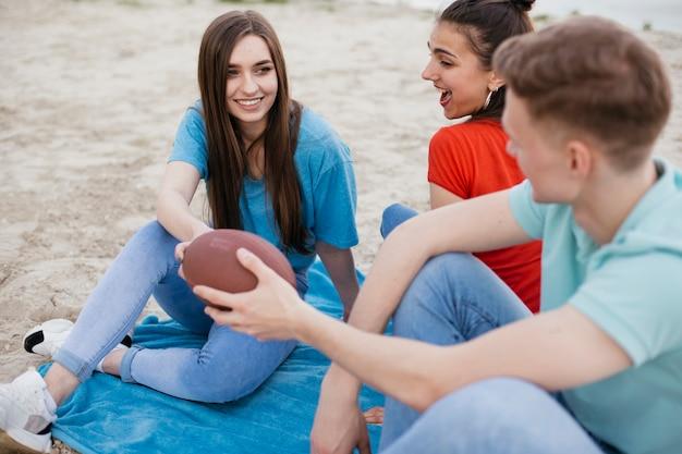 Amici felici dell'angolo alto con la palla di calcio