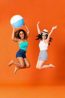 Amici felici della donna in vestiti casuali di estate che saltano