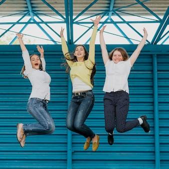 Amici felici della foto a figura intera che saltano insieme