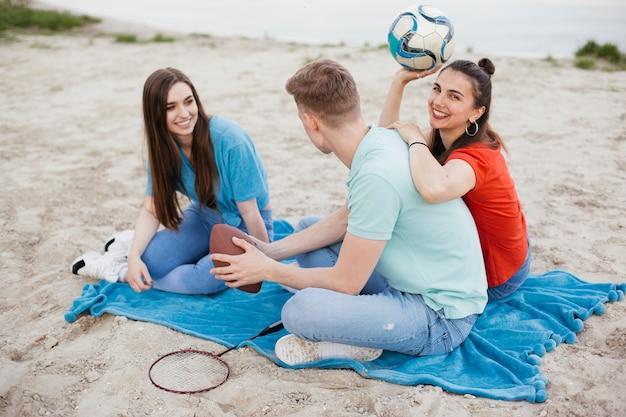 Amici felici della foto a figura intera che si siedono sulla spiaggia