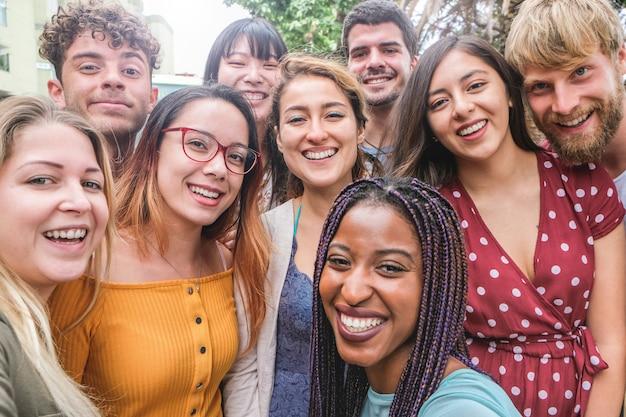 Amici felici di diverse culture e razze che scattano foto facendo facce buffe - generazione millenaria e concetto di amicizia con i giovani che si divertono insieme - focus principale sulla ragazza con gli occhiali