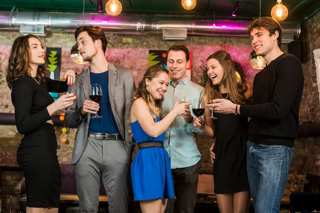 Amici felici di sesso maschile e femminile, bere e tostare cocktail in un bar