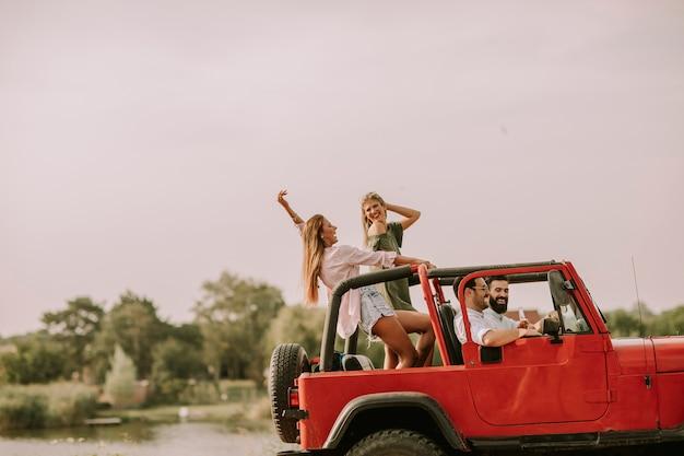 Amici felici divertendosi in auto convertibile in vacanza