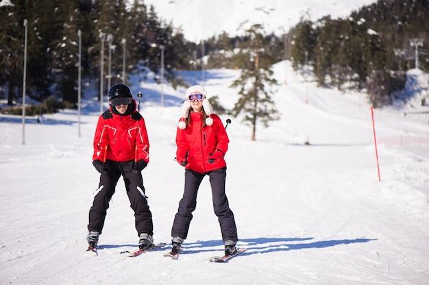 Amici felici divertendosi nella stazione sciistica delle montagne - natura e immagine di sport.