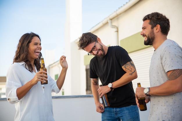 Amici felici eccitati che bevono birra, chiacchierano e ridono