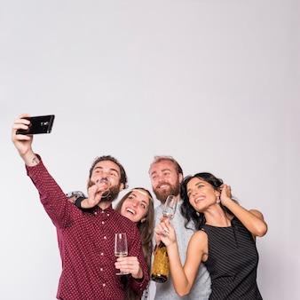 Amici felici facendo selfie con champagne