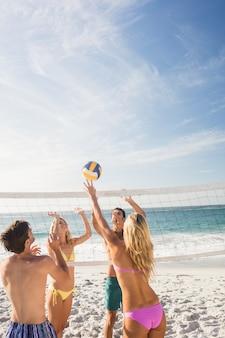 Amici felici giocando a beach volley
