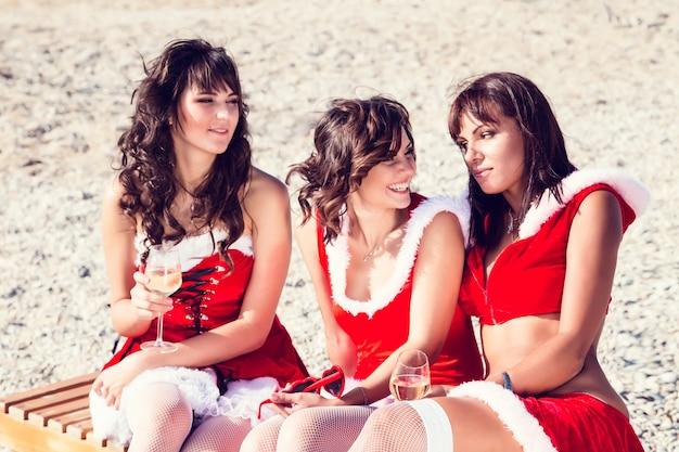 Amici felici in cappelli di santa sulla spiaggia. vacanze di natale