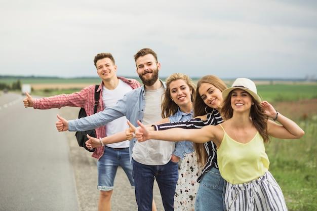 Amici felici in piedi in fila sulla strada autostop