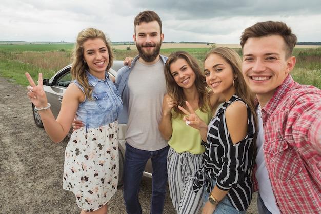 Amici felici in piedi vicino all'automobile prendendo selfie