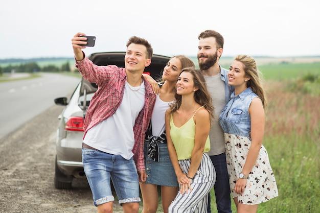Amici felici in viaggio su strada prendendo selfie su smartphone