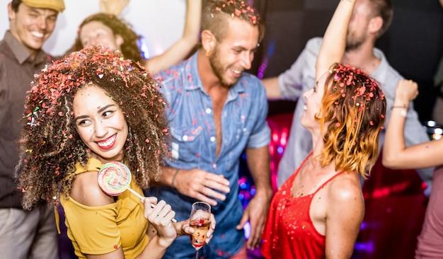 Amici felici multirazziali divertirsi bevendo vino alla festa di vigilia