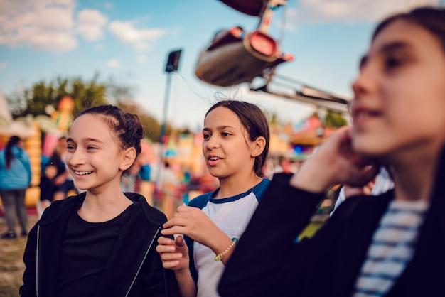Amici felici vanno in giro al parco divertimenti