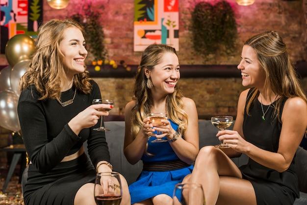 Amici femminili abbastanza giovani nella barra che gode delle bevande