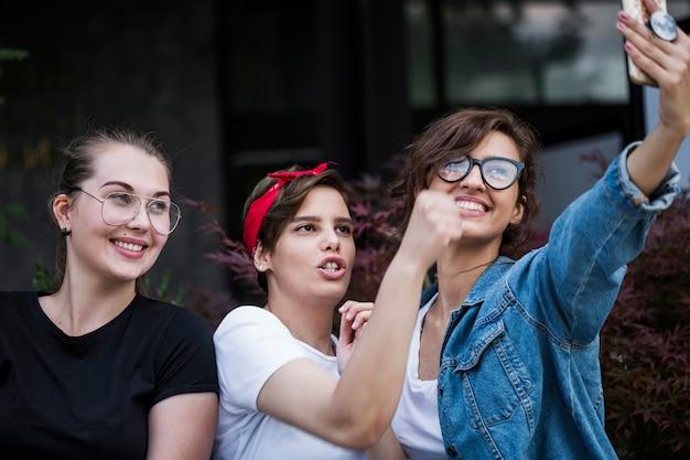Amici femminili allegri che prendono selfie nel parco