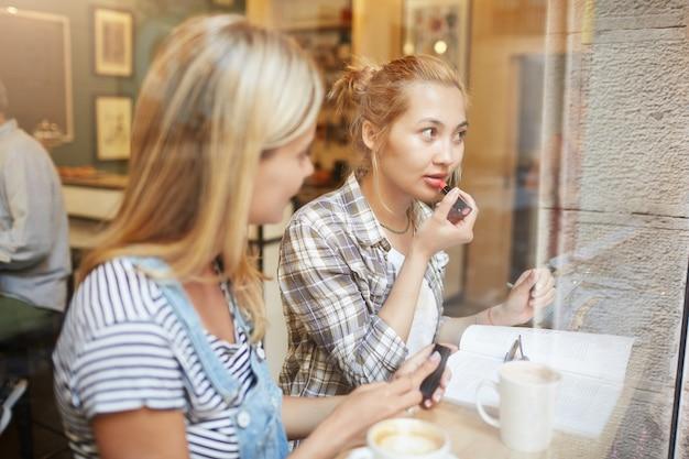 Amici femminili biondi che si siedono nella caffetteria