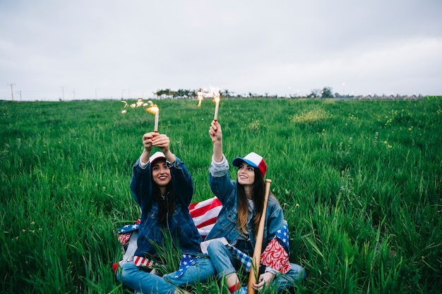 Amici femminili che celebrano la festa dell'indipendenza su erba verde