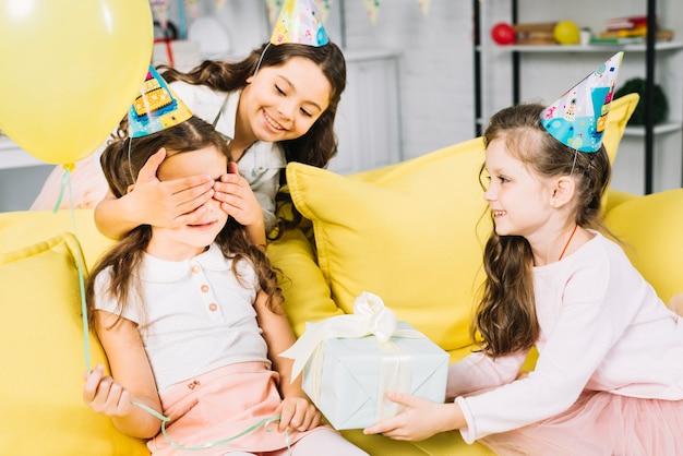 Amici femminili che danno regalo alla ragazza di compleanno a casa