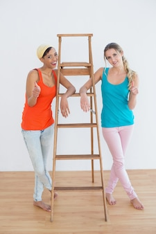 Amici femminili che gesturing i pollici su contro la scala in nuova casa