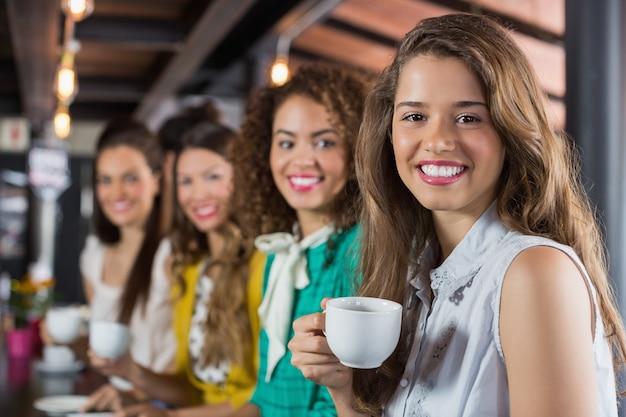 Amici femminili che mangiano caffè nella caffetteria