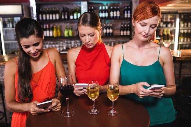 Amici femminili che per mezzo del telefono cellulare mentre godendo del vino