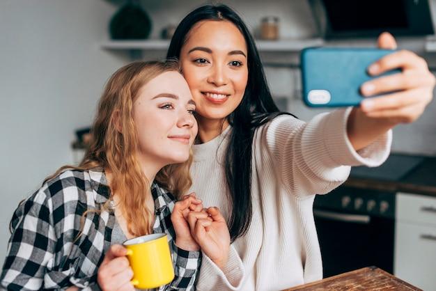 Amici femminili che prendono selfie a casa