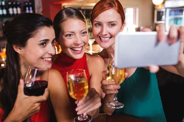Amici femminili che prendono selfie con il bicchiere di vino in night-club