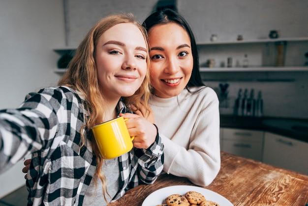 Amici femminili che prendono selfie in cucina