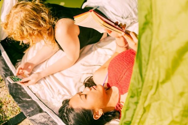 Amici femminili che si rilassano mentre trovandosi in tenda