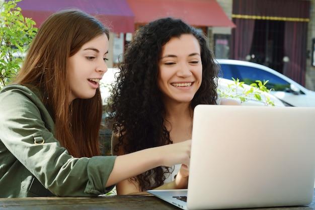 Amici femminili che studiano con un computer portatile in una caffetteria.