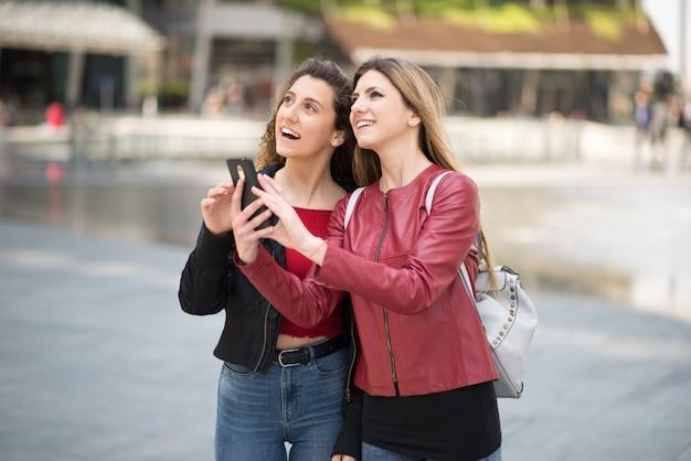 Amici femminili che usando insieme il loro telefono cellulare