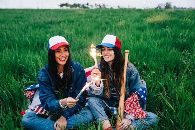 Amici femminili con i fuochi d'artificio che si siedono nel campo
